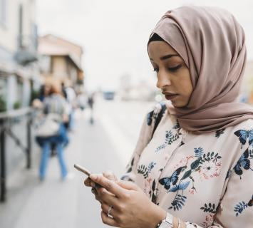 woman outside wearing hijab looking at her mobile phone