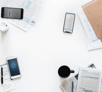 mobile phones and paperwork on a white table