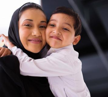 Smiling lady in a hijab hugging her son