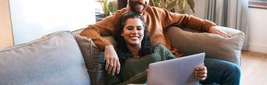 Man and woman on a sofa looking at a laptop