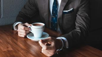 Man wearing suit drinking a coffee