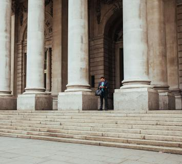 Man standing outside of a building between two pillars