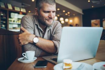 Man looking at laptop with and espresso in a coffee shop