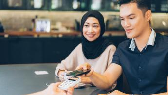 Man using cardless payment sat next to smiling woman
